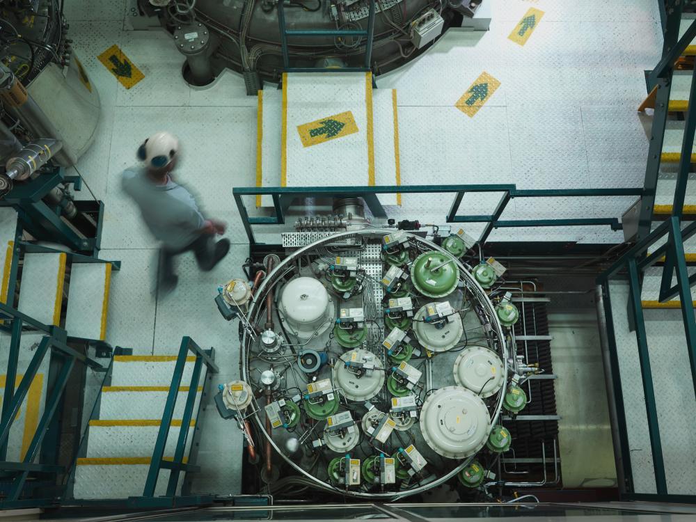 A man in a hard hat walks through a nuclear reactor plant floor.