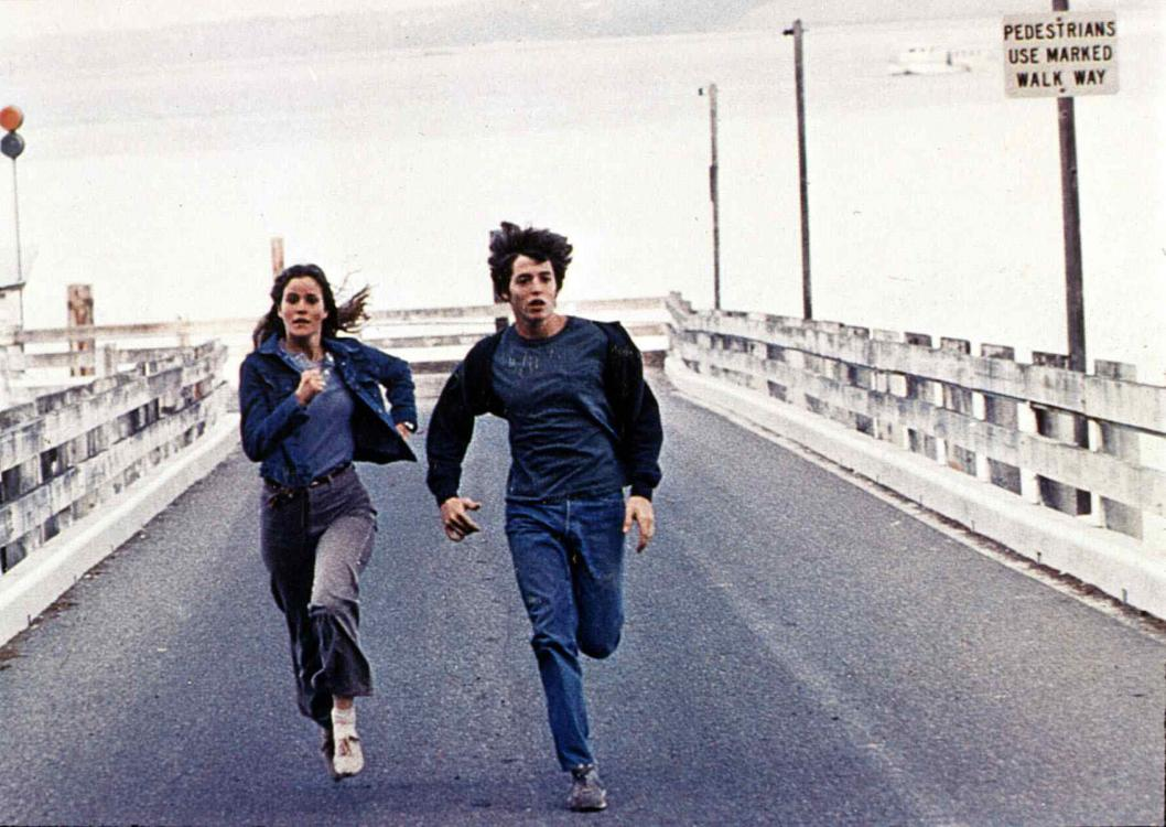 A young man and a young woman  run down a pier.