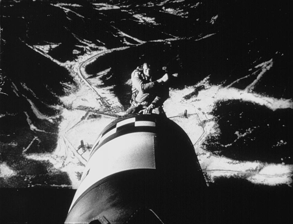 A man rides on a nuclear bomb, depicted in mid-flight.