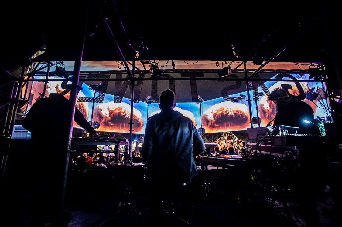 A view of a concert, from behind the band, with projected images of a nuclear mushroom cloud.