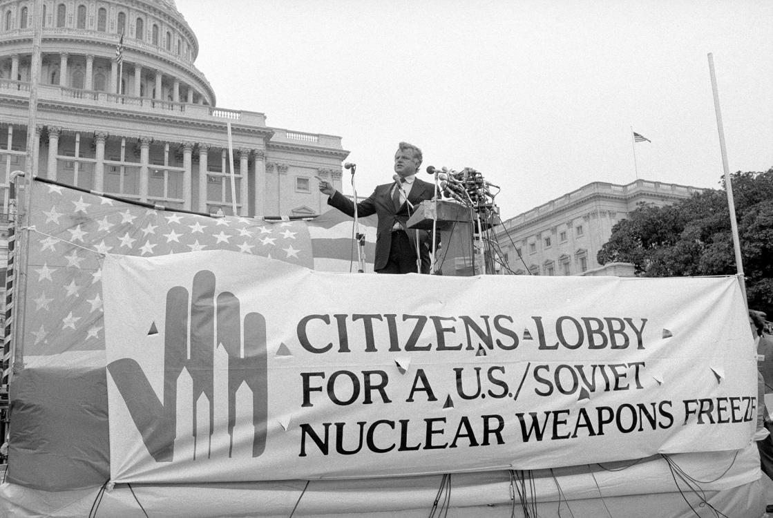"In front of the Capitol Building, a man gives a speech into a podium crowded with microphones. The man is standing next to an American Flag, and in front of a banner that reads, ""Citizens lobby for a U.S./Soviet nuclear weapons freeze"". A logo on the sign depicts a halting hand help up to four nuclear missiles."