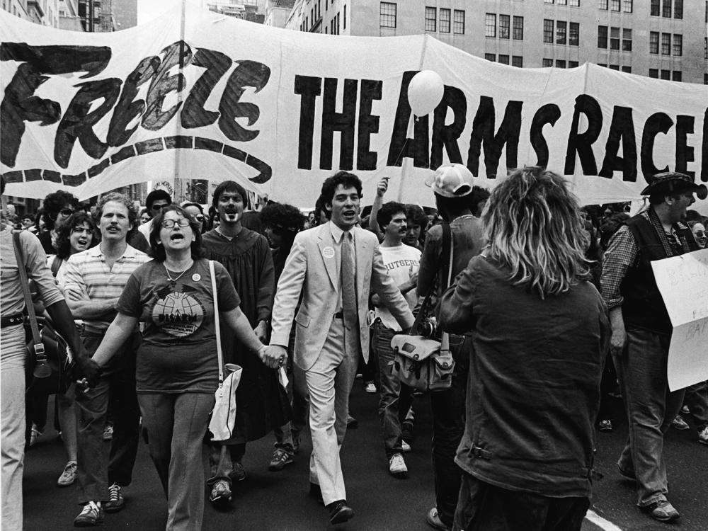 A man in a suit leads a protesting crowd holding a banner that reads, 'Freeze the arms race'.