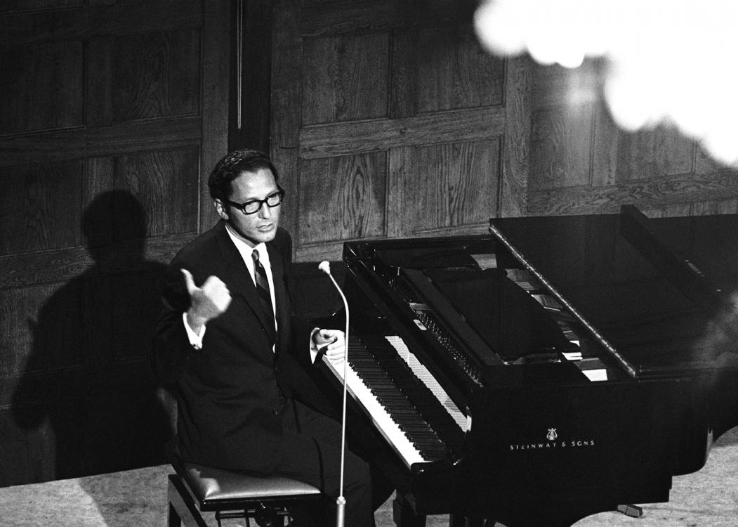 A man in thick-rim glasses and a black suit talks at a microphone from the bench of a piano.