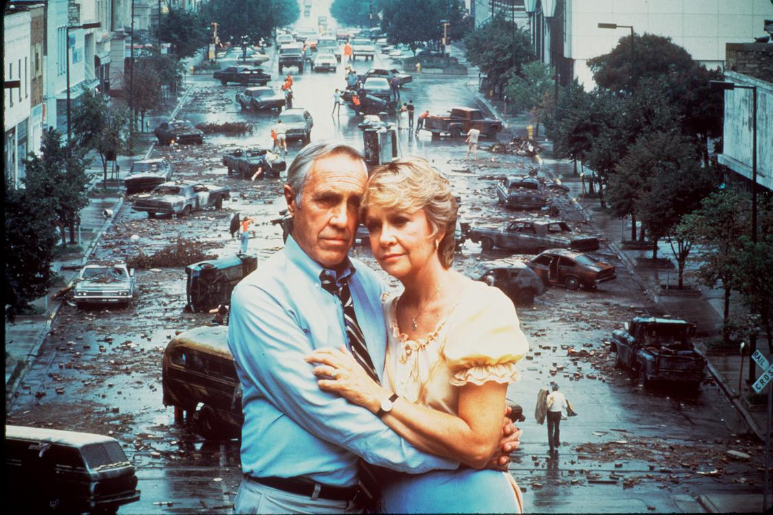Two people embrace each other in front of a street full of abandoned cars. A still from The Day After.