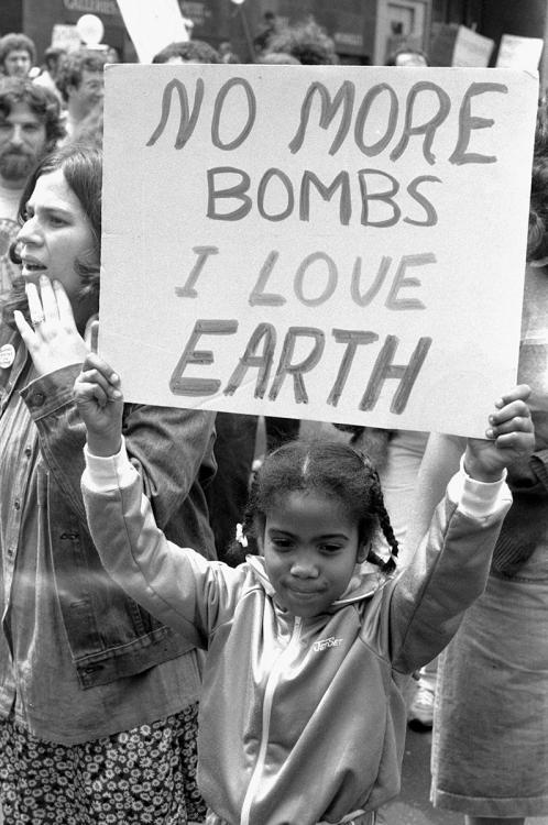"A young girl holds a sign that reads, ""No more bombs I love Earth""."