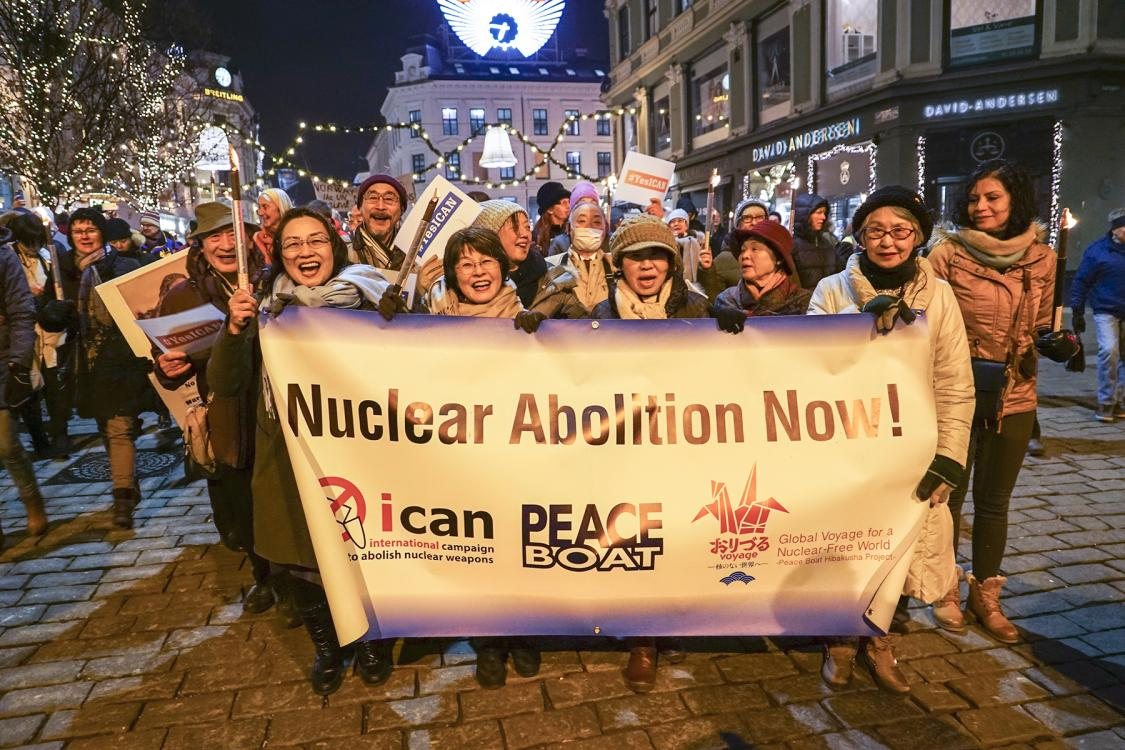 A group of women march behind a sign that reads, 'nuclear abolition now'.