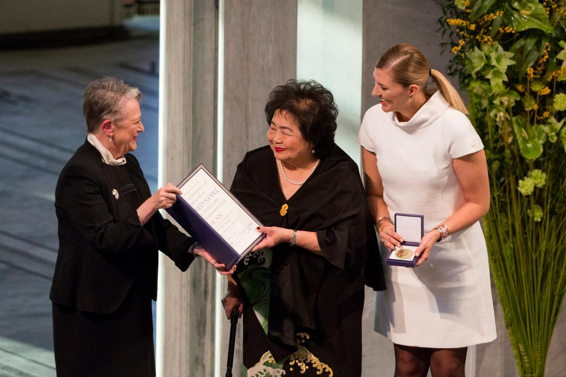 Setsuko Thurlow and Beatrice Finn accept an award on a stage.