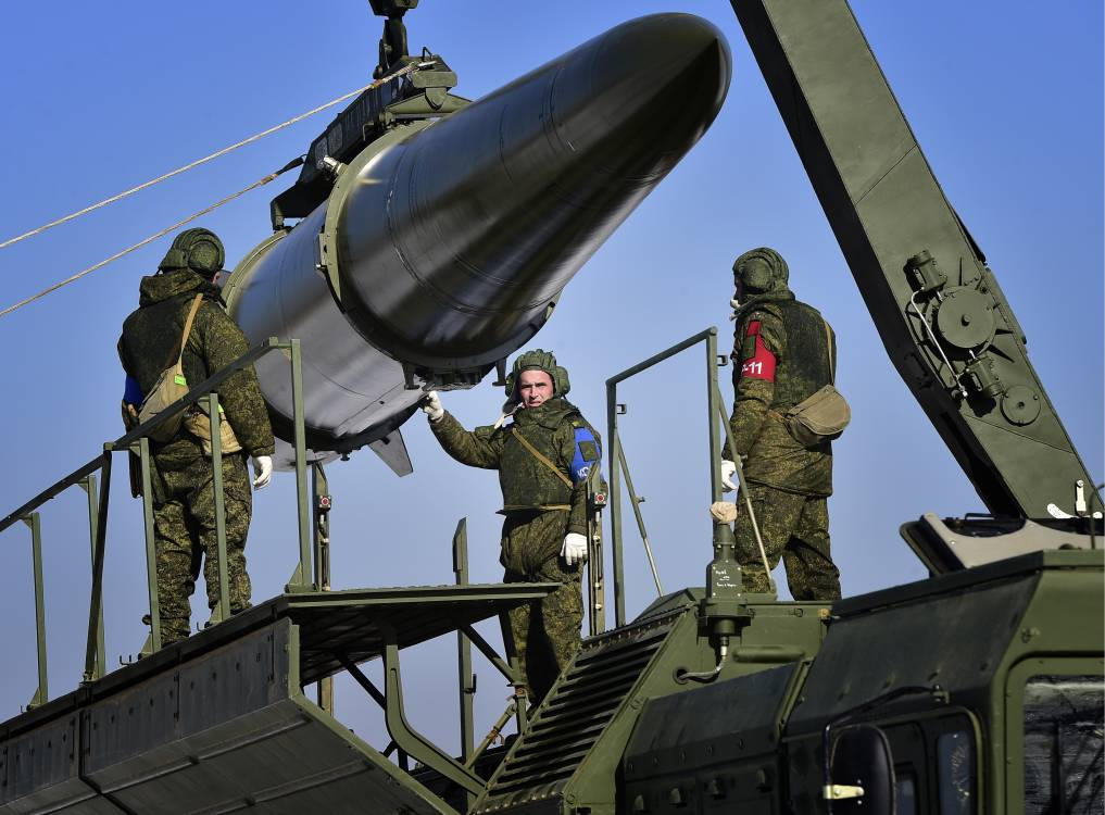 three soldiers handle a missile.