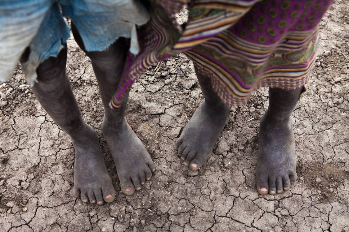 feet of two children standing on a dry riverbed