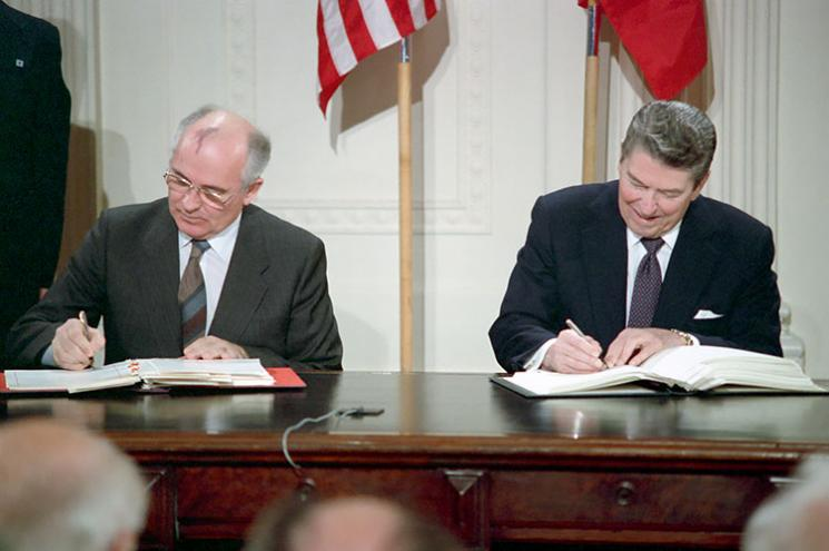Gorbachev and Reagan sit in the East Room of the White House signing the INF Treaty in front of reporters