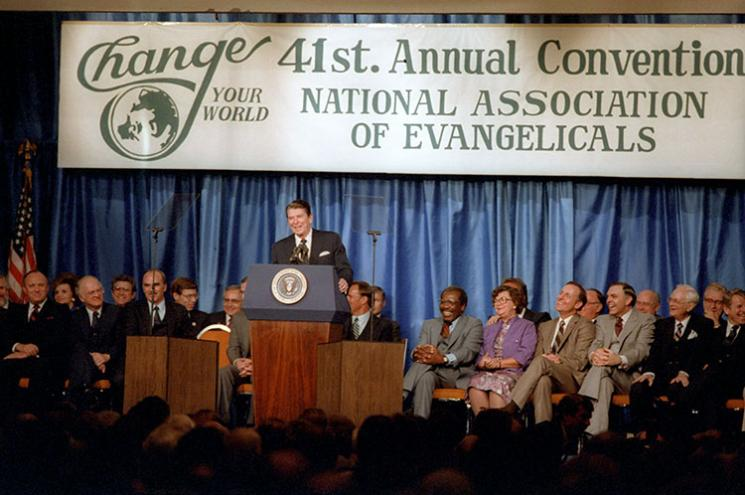 Ronald Reagan stands at a podium, addressing a crowd.