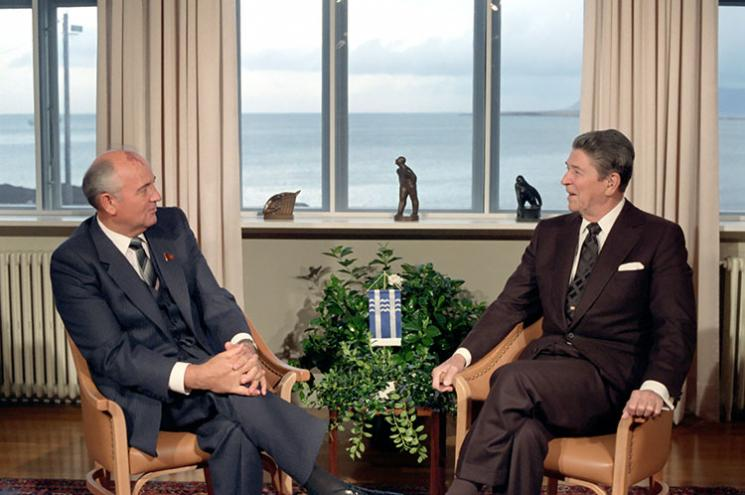Reagan and Gorbachev sit and talk to each other.