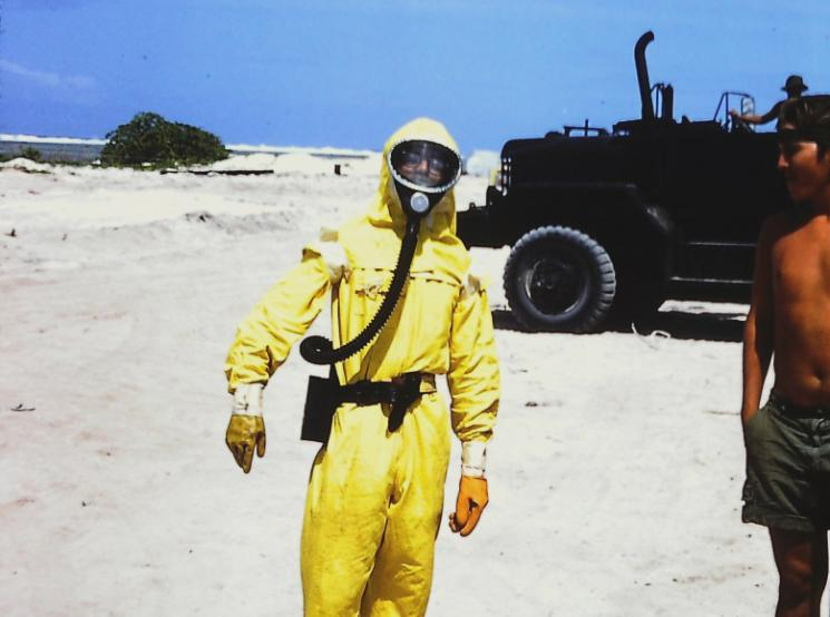 A young man wearing a yellow radiation suit and face mask stands on a beach near a shirtless man wearing a ball-cap.
