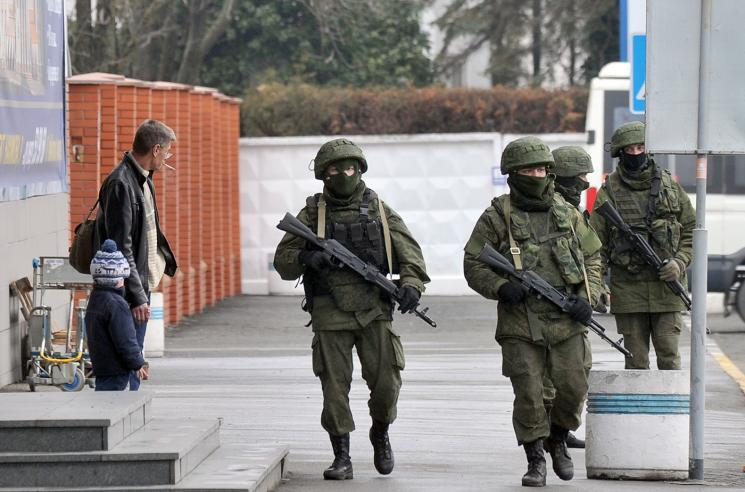 Four masked soldiers, with rifles slung around their necks', walk past a father and son on a grey sidewalk.