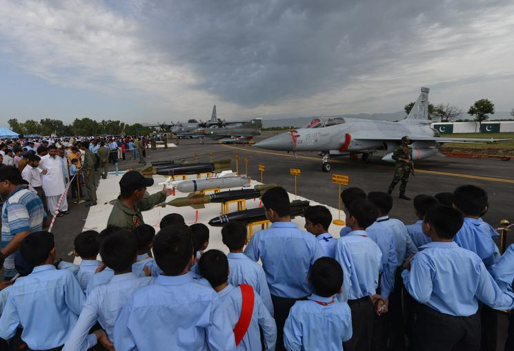 A group of school children stand on a tarmac airstrip and watch a man point towards a series of missiles that are displayed in a row.