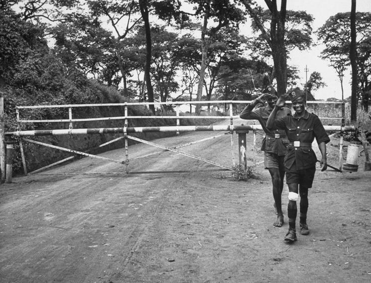 Two men in short-sleeve uniforms stand on a dirt road in front of a closed gate.