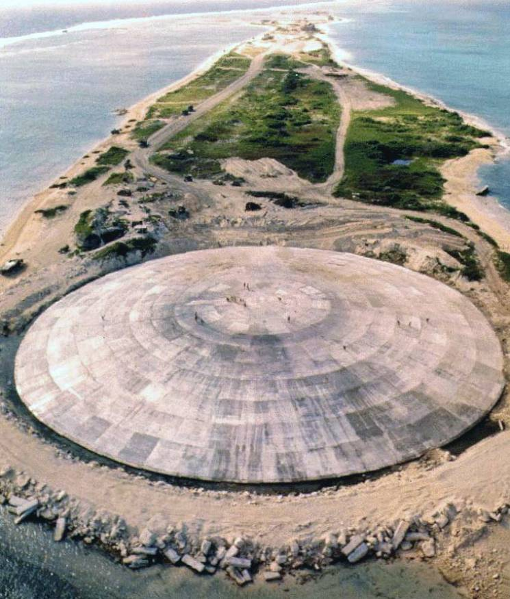 A giant cement dome dominates a small atoll. Small specks of people can be seen walking across the dome; the island stretches into the background.