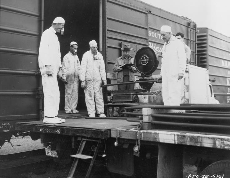 People in white jumpsuits and respirators stand around a scale next to a railcar.