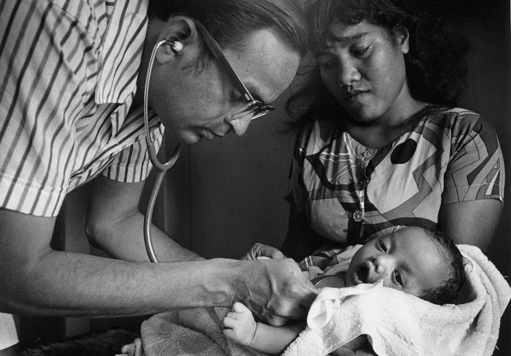 A doctor listens to the heartbeat of an infant, in the presence of a concerned mother.