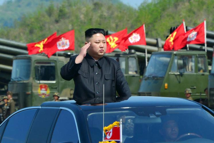 Kim Jong Un stands out of the sunroof of a car and salutes.