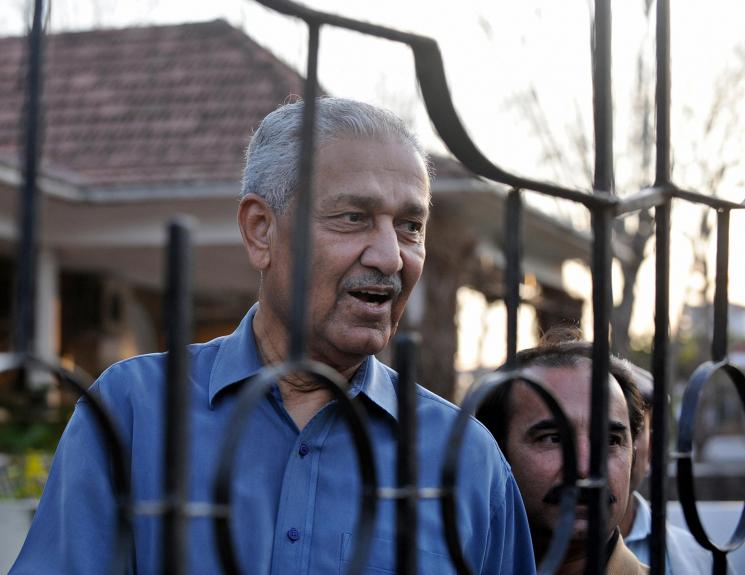 An older man is visible beyond a gate, he appears to be speaking to someone out of frame.