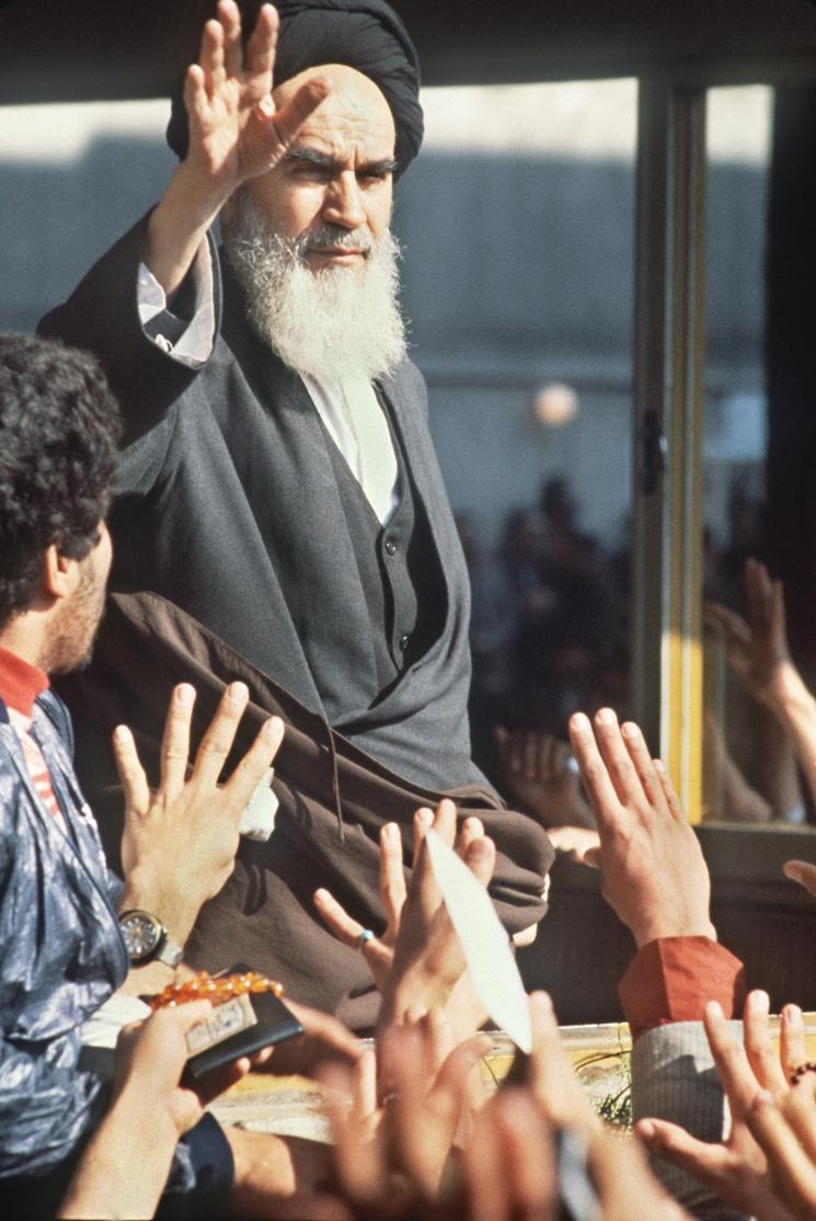 Ayatollah Khomeini, dressed in a head wrap and a long white beard, holds his hand up to a reaching crowd.