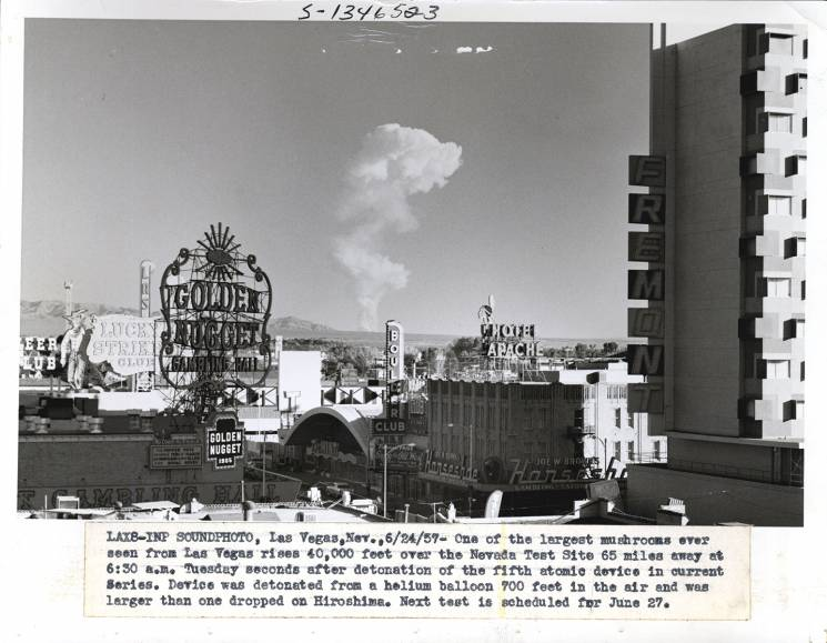 A mushroom cloud is seen in the background behind a Las Vegas skyline. Neon casino signs can are seen in the foreground.