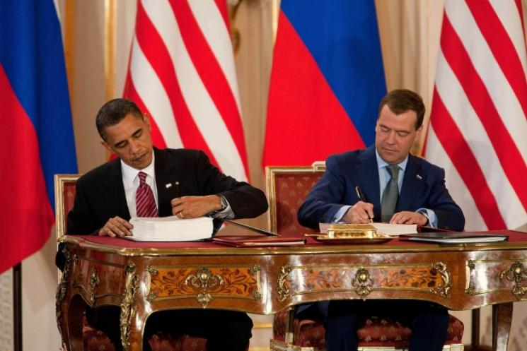 President Barack Obama and Russian president Dmitry Medvedev sit side-by-side, their countries' flags in the background.