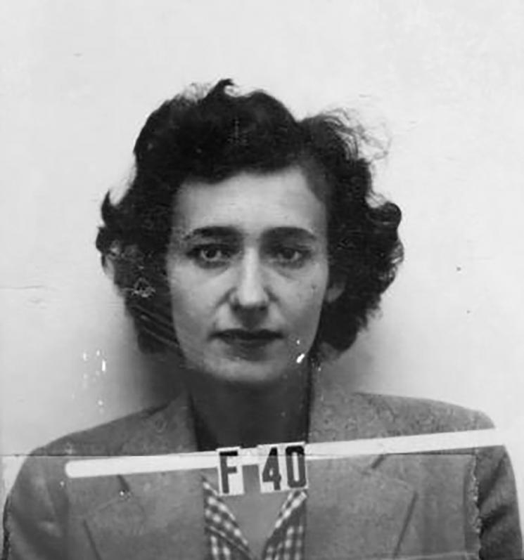 A mugshot style photograph of a woman with short curly hair, wearing a suit and a gingham button-down shirt.