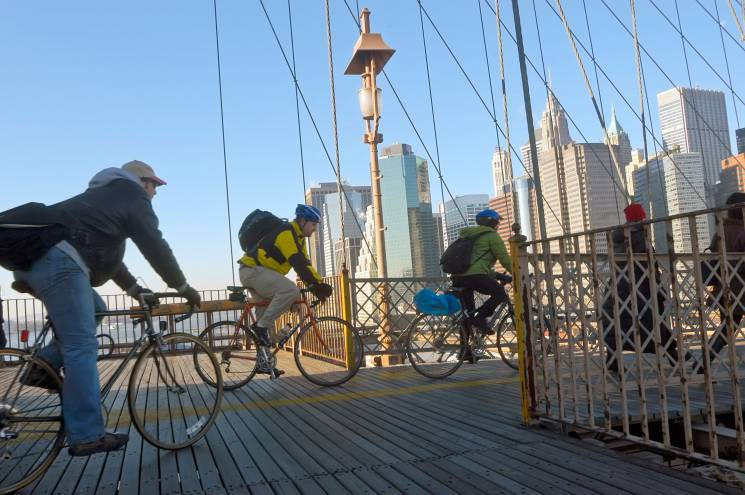 Bike commuters cross a bridge in New York City. Driving less often is one way to reduce your personal impact on the climate.