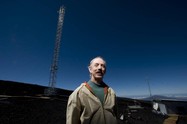 A scientist stands near a meteorological observation tower in Hilo, Hawaii.