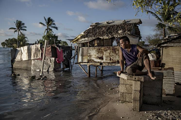 A resident of the village of Eita in Kiribati watches the ocean flood his hometown.  The island lies only a few feet above sea level, putting it at risk for flooding and sea swells.
