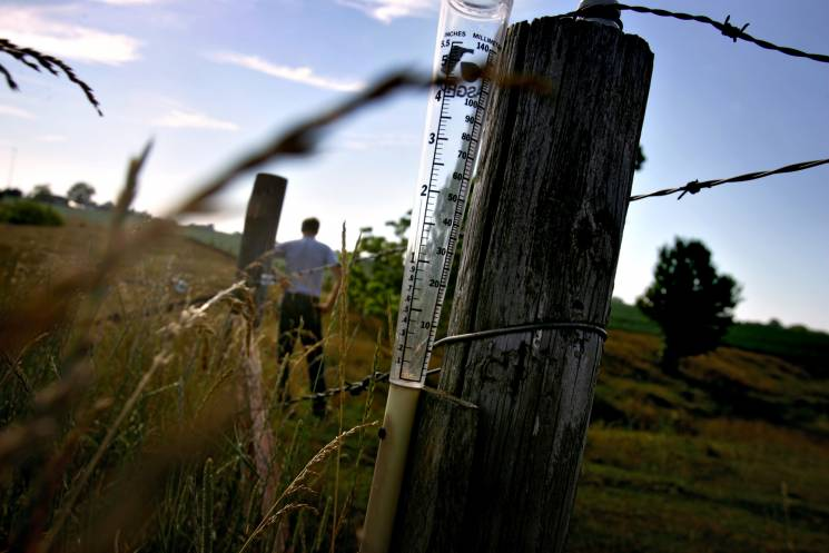 An empty rain gauge sits on a fence post on an Illinois farm.