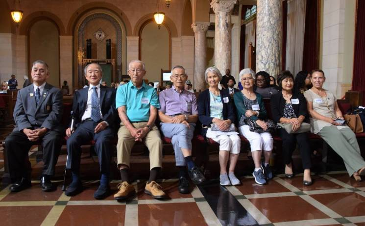 older adults sit in a row