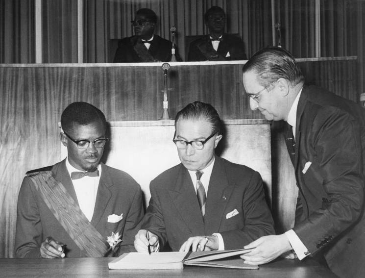 two men sign papers seated at desk