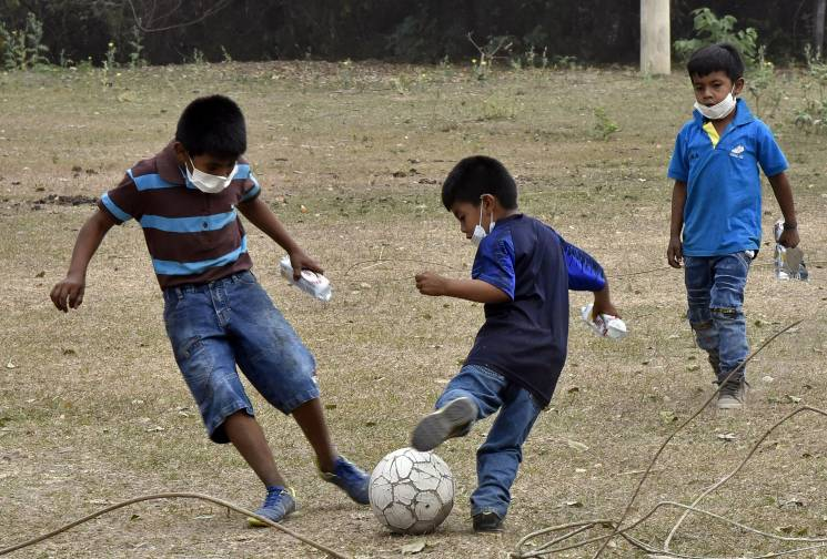 Boys of the community of Quitunuquina, in the surroundings of Robore in eastern Bolivia, play football with surgical masks due to the forest fires in the area, on August 25, 2019.