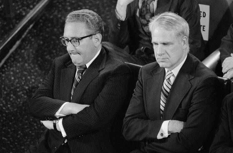 men sit side by side with arms crossed