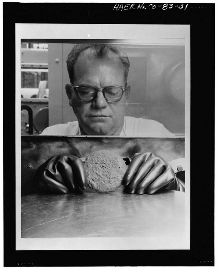 man holds plutonium button