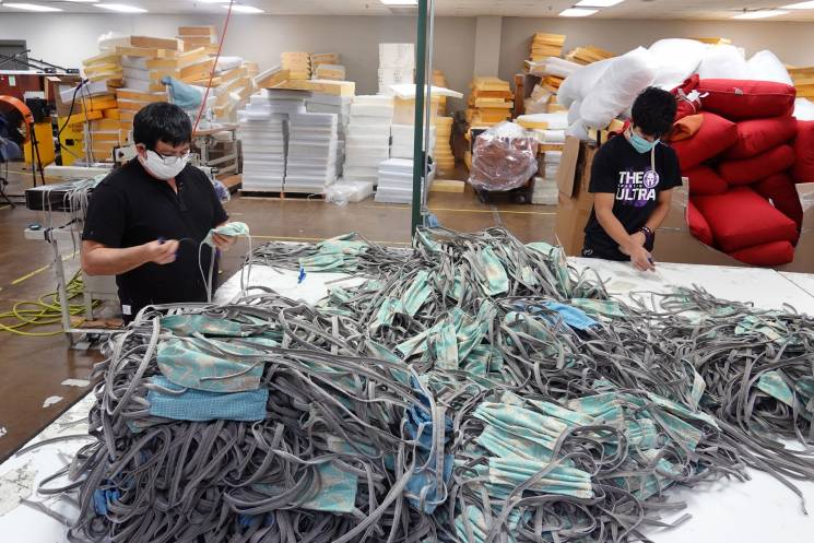 factory worker by a pile of masks