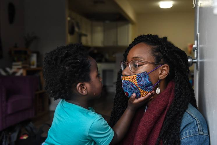 Woman with a medical mask on looks at her son