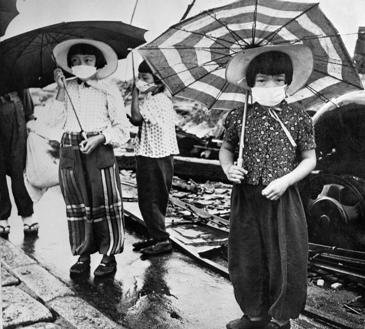 girls with parasols and face masks