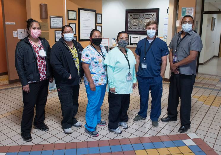 medical staff pose in a line with masks covering their faces