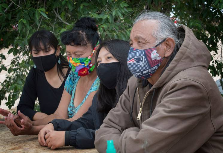family sits at a table all with masks covering their mouths and noses