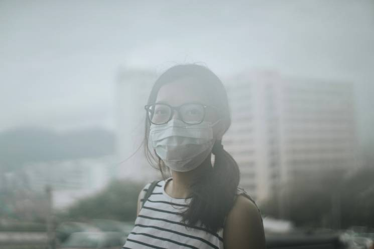 Young woman wearing protective face mask outdoors due to the polluted air; Getty