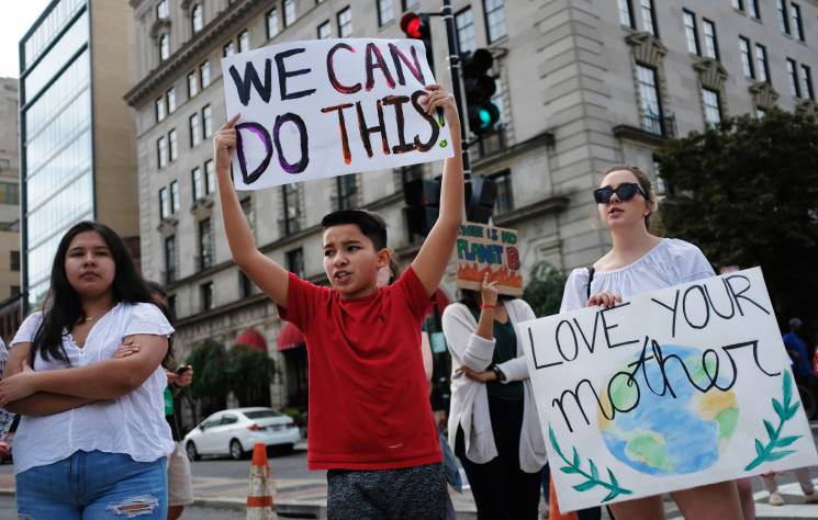 A young protestor holds a placard while demonstrating at an intersection in Washington, DC on September 23, 2019.; Getty