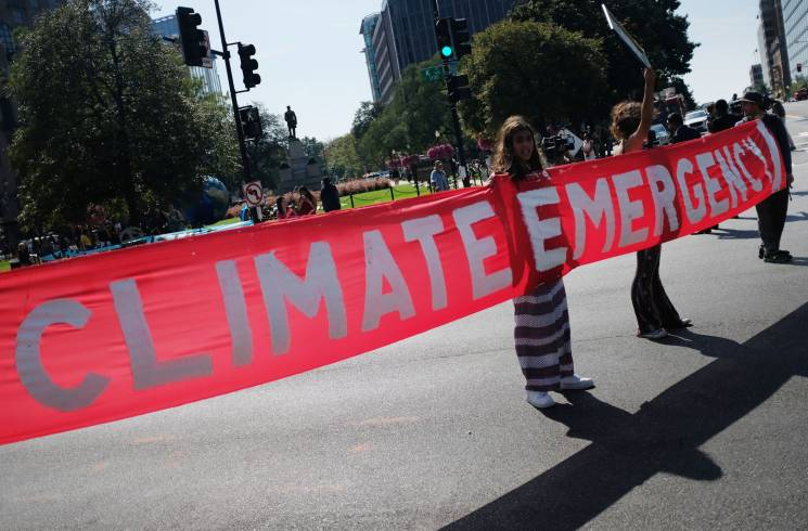 Activists hold a banner while blocking a major intersection during climate protests in Washington, DC on September 23, 2019; Getty