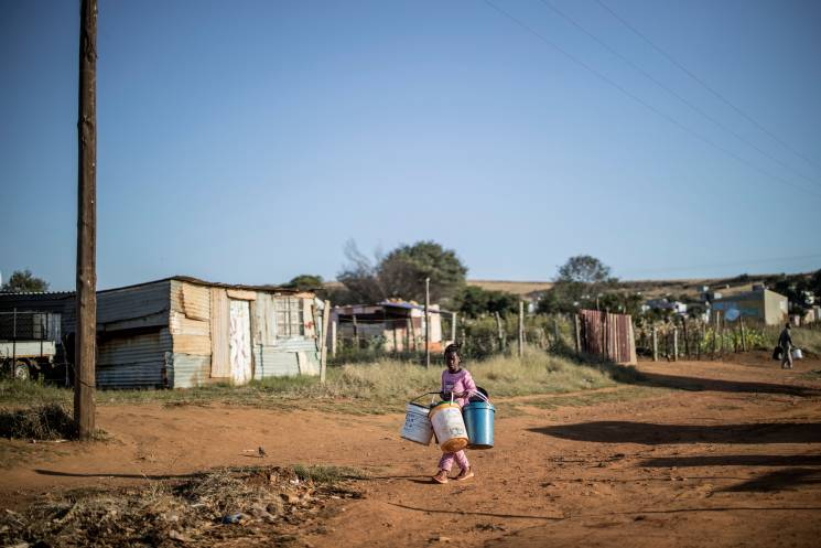 A young resident of the informal settlement on the outskirts of Lawley, Johannesburg, on April 24, 2020 carries her buckets as she approaches a water tanks dispatched by the municipality to help the community to cope with water scarcity; Getty