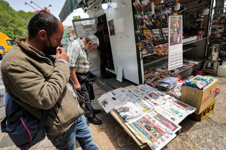 men read newspapers at news stand