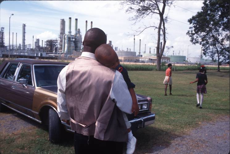"""A family leaves Sunday church services surrounded by chemical plants in October of 1998 in Lions, Louisiana. The poor, often black towns along the Mississippi River near Baton Rouge are known as """"Cancer Alley"""" for the high cancer clusters and the many chemical and oil production factories."""