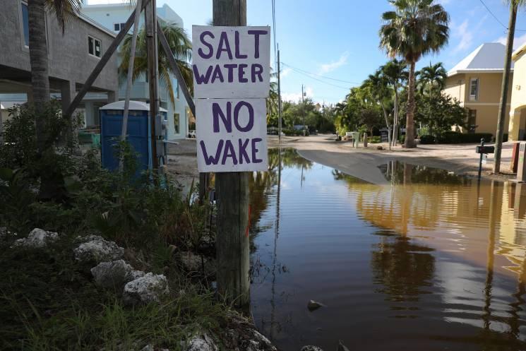 Un cartel dice, Salt Water No Wake', mientras el agua del océano inunda una calle en Cayo Largo, Florida el 22 de octubre. La marea King, junto con unas tormentas previas, empujaron agua marina hacia las calles en partes de los Cayos en Florida, que probablemente vean un incremento en las inundaciones a medida que el nivel del mar continúa subiendo.